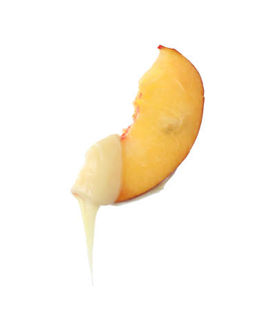 Fondue fork with slice of peach dipped into chocolate on white background Banque d'images