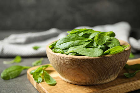 Fresh green healthy spinach on grey table Stock Photo