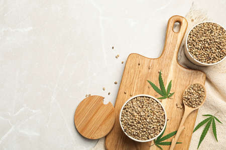 Flat lay composition with hemp seeds and leaves on beige marble background, flat lay. Space for text Stock Photo