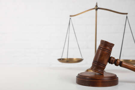 Composition with gavel and scales of justice on table against white background, space for text. Criminal law