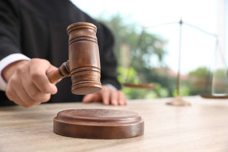 Judge with gavel at wooden table indoors, closeup. Criminal law