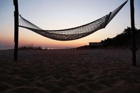 Empty hammock on beach at sunset. Time to relax 版權商用圖片