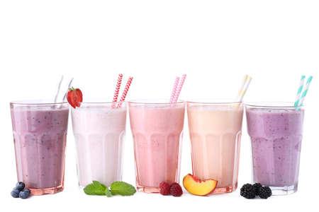 Diferentes batidos de leche sabrosos frescos en vasos con ingredientes sobre fondo blanco.