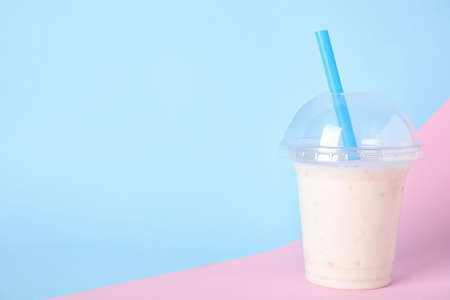 Tasty milk shake in plastic cup on color background. Space for text