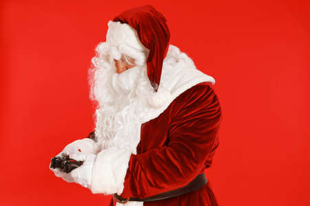 Authentic Santa Claus with game controller on red background Stock Photo