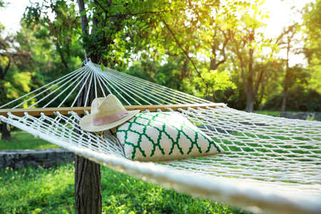 Comfortable net hammock with pillow and hat hanging in green garden