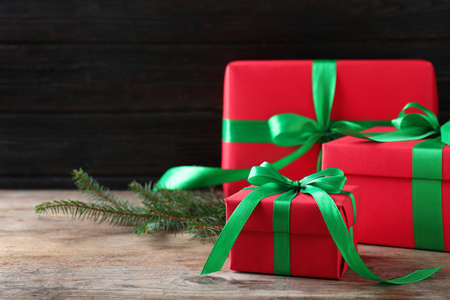 Christmas gifts on wooden table against dark background. Space for text Stockfoto