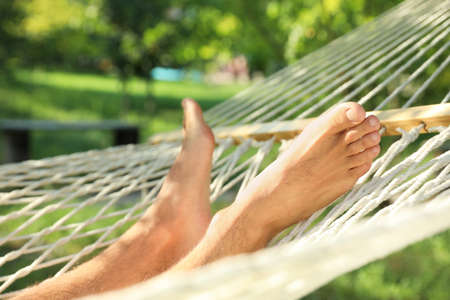 Young man resting in comfortable hammock at green garden, closeup