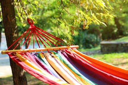 Bright comfortable hammock hanging in green garden, closeup