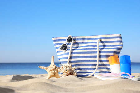 Set with stylish beach accessories on sand near sea