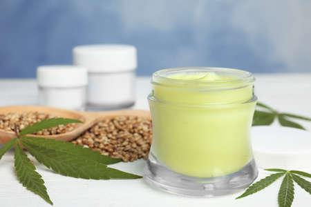 Glas Hanfcreme und Samen auf weißem Holztisch vor blauem Hintergrund, Nahaufnahme. Bio-Kosmetik