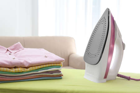 Board with modern iron and clean laundry at home