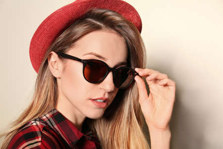 Young woman wearing stylish sunglasses on beige background