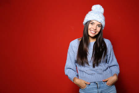 Young woman in warm sweater with hat on red background. Space for text