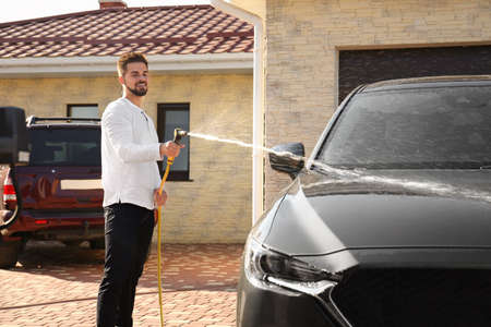 Young happy man washing car at backyard on sunny day Stock fotó