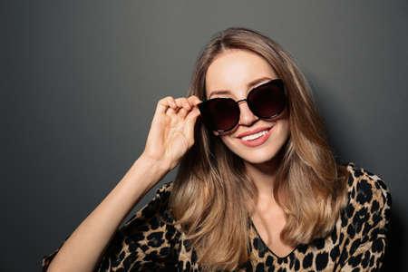 Young woman wearing stylish sunglasses on dark grey background Stock fotó