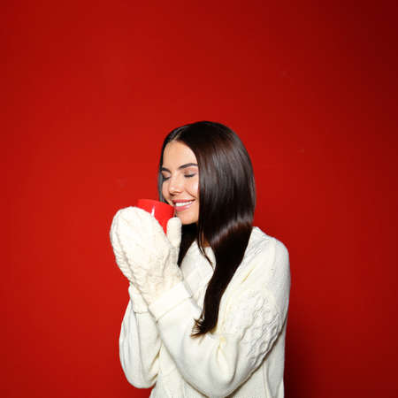 Young woman in warm sweater with cup of hot drink on red background Stock fotó