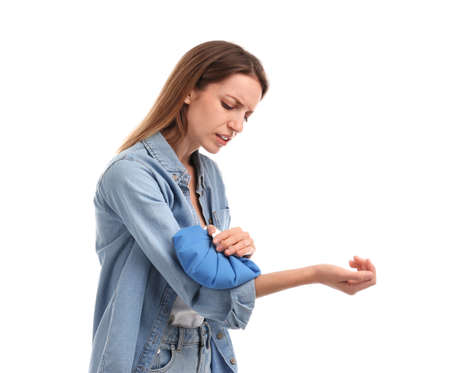 Woman applying cold compress to relieve arm pain on white background Imagens