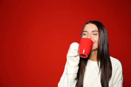 Young woman in warm sweater with cup of hot drink on red background. Space for text