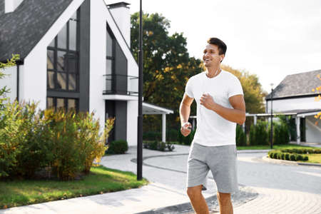Young man with earphones running outdoors on sunny morning. Healthy lifestyle Stock fotó