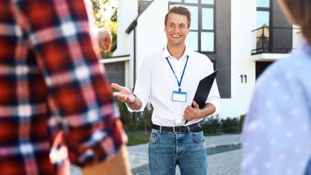 Real estate agent showing house to young couple outdoors 스톡 콘텐츠