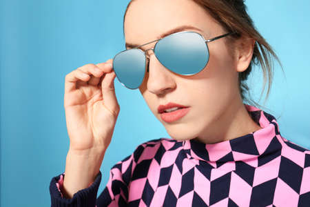 Young woman wearing stylish sunglasses on blue background