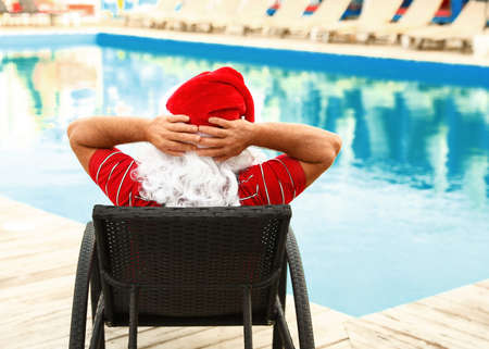 Authentic Santa Claus resting on lounge chair near pool at resort, back view