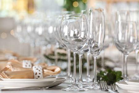 Nakrycie stołu z pustymi szklankami, talerzami i sztućcami w pomieszczeniu Zdjęcie Seryjne