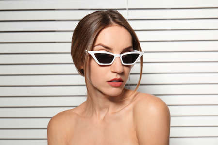 Young woman wearing stylish sunglasses against blinds Stock fotó