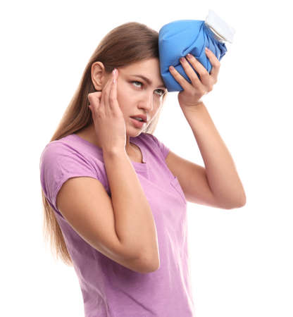 Unhappy woman using cold pack to cure headache on white background