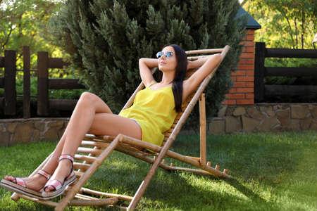 Beautiful young woman relaxing in deckchair at garden