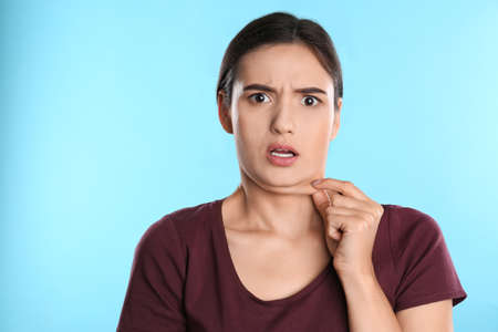 Emotional young woman with double chin on blue background