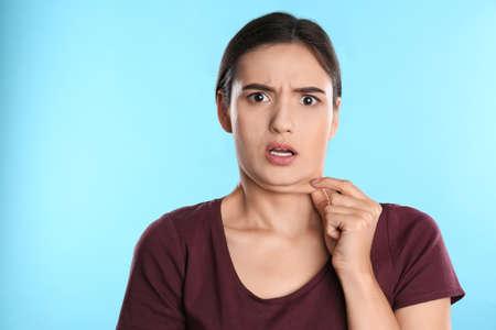 Giovane donna emotiva con doppio mento su sfondo blu Archivio Fotografico