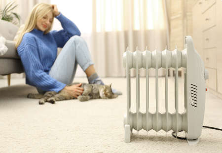 Electric heater and blurred young woman with cute tabby cat on background. Space for text