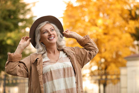Portrait of happy mature woman with hat outdoors Stock Photo