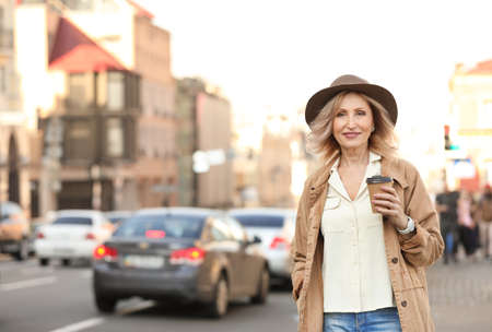 Mature woman with cup of coffee on city street