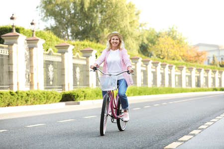 Mature woman riding bicycle outdoors. Active lifestyle Stock Photo