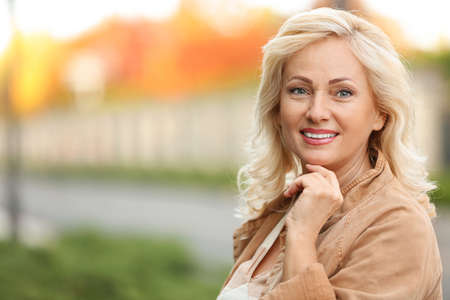 Portrait of happy mature woman on city street Stock Photo