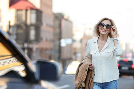 Beautiful mature woman with sunglasses on city street