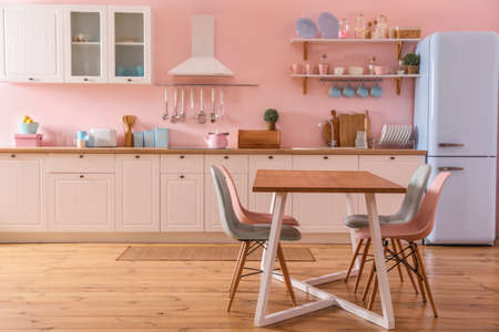 Stylish pink kitchen interior with dining table and chairs 스톡 콘텐츠