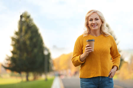 Beautiful mature woman with cup of coffee outdoors Stock Photo