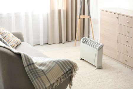 Calentador eléctrico moderno en el interior de la habitación con estilo Foto de archivo