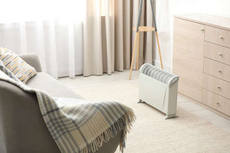 Modern electric heater in stylish room interior