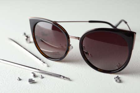Stilvolle weibliche Sonnenbrillen und Befestigungswerkzeuge auf weißem Tisch Standard-Bild