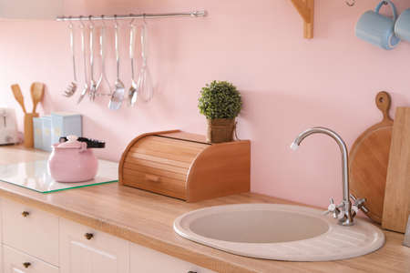 Stylish kitchen with sink and clean dishware near pink wall