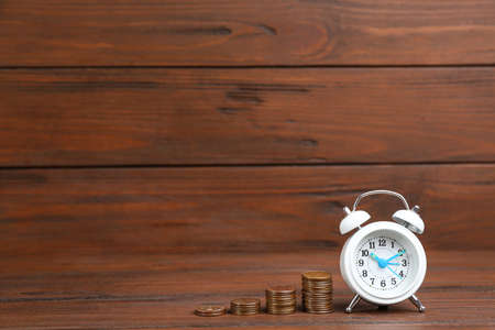 White alarm clock and stacked coins on table against wooden background, space for text. Money savings