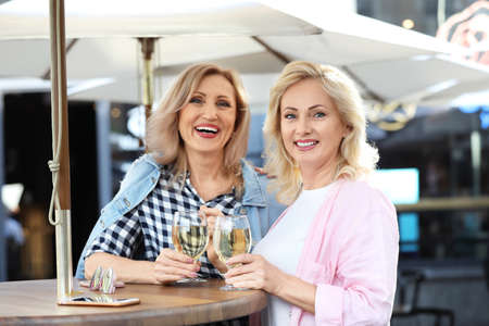 Mature women with drinks at outdoor cafe Stock Photo