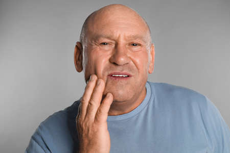 Mature man suffering from toothache on light grey background Stock Photo
