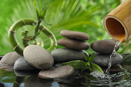 Composition with stones and bamboo fountain against blurred background. Zen concept