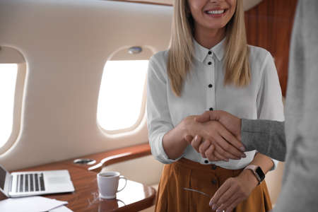 Young people shaking hands after bargaining on plane, closeup. Business deal